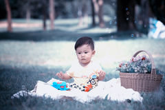 Asia Baby boy sitting on green grass with soap bubbles Stock Image