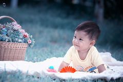 Asia Baby boy sitting on green grass with soap bubbles Royalty Free Stock Image