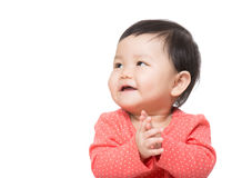 Asia baby girl clapping hand and looking at aside Stock Image