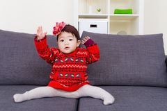 Asia Baby girl doing legs splits on sofa Stock Photo