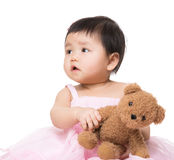 Asia baby girl looking aside and play with doll Stock Images