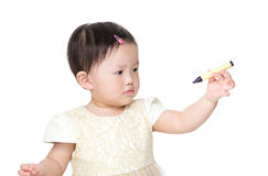 Asia baby girl looking at crayon. Isolated on white Royalty Free Stock Image
