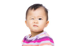 Asia baby girl with one winking eye. Isolated on white stock photo