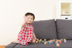 Asia baby girl play toy block and sitting on sofa Stock Images