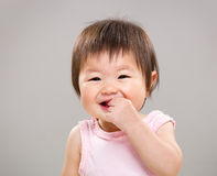 Asia baby girl put finger into mouth Royalty Free Stock Image
