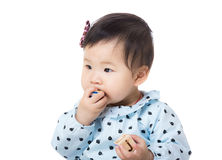 Asia baby girl put wooden toy block into mouth Stock Images