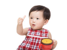 Asia baby girl with snack box and thumb up. Isolated on white Royalty Free Stock Photography
