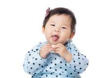 Asia baby girl suck toy block into mouth Stock Photos
