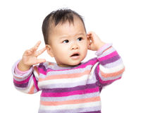 Asia baby girl touch her ear Royalty Free Stock Images