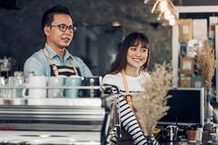 Asia Barista waiter smile and talking to customer in coffee shop. Two cafe owner at counter bar,Food and drink business concept,Service mind concept Royalty Free Stock Image