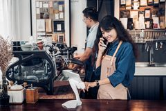 Asia Barista waiter use tablet take order from customer in coffe. E shop,cafe owner writing drink order at counter bar,Food and drink business concept,Service Stock Images
