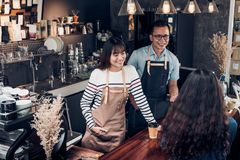 Asia barista waiter and waitress take order from customer in cof. Fee shop,Two cafe owner writing drink order at counter bar,Food and drink business concept Stock Image