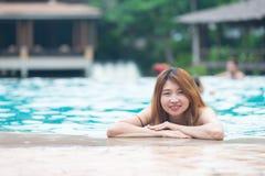 Asia beautiful Woman at the Edge of Swimming Pool stock photo