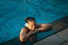 Asia beautiful woman relaxing at the Edge of Swimming Pool stock image