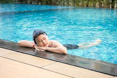 Asia beautiful Woman relaxing at the Edge of Swimming Pool. Beautiful Woman relaxing at the Edge of Swimming Pool stock photos