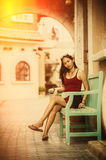 Asia beautiful woman sit relax on green wood chair. Asia beautiful woman sit relax on wood chair at the city royalty free stock images