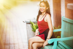 Asia beautiful woman sit relax on green wood chair. Portrait of Asia young pretty girl in park royalty free stock photography