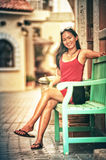 Asia beautiful woman sit relax on green wood chair. Portrait of Asia young pretty girl in park royalty free stock photos