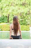 Asia beautiful woman sitting on edge of the pool Royalty Free Stock Image