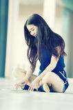 Asia beautiful young girl with tablet on floor Stock Image