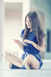 Asia beautiful young girl with tablet on floor Royalty Free Stock Image