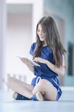 Asia beautiful young girl with tablet on floor Royalty Free Stock Photos