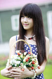 Asia beauty outdoor portrait. Asia beauty holding a basket of flowers outdoor portrait Royalty Free Stock Photos