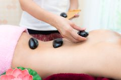 Asia beauty woman lying down on massage bed with traditional balinese hot stones along the spine at Thai spa and wellness center, royalty free stock photos