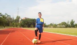 Asia boy playing Soccer football field stadium. Stock Image