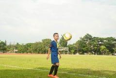 Asia boy playing Soccer football field stadium grass line ball b Royalty Free Stock Photos