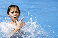 Asia boy is playing in water. Teenager chinese body is making cool gesture in the pool Royalty Free Stock Image