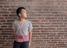Asia boy stand front wall brick old age Stock Photography