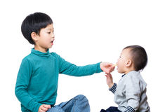 Asia brother giving biscuit to his little brother Royalty Free Stock Images