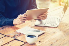 Asia business man using tablet and laptop on table in coffee sho Stock Images