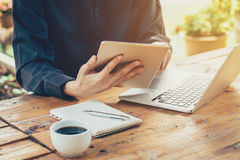 Asia business man using tablet and laptop on table in coffee sho Stock Image