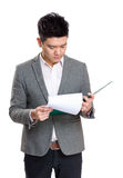 Asia businessman concentrate reading on clipboard. Isolated on white Royalty Free Stock Image