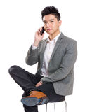 Asia businessman sitting on chair and talking to mobile Stock Photography