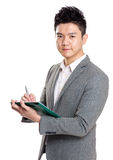 Asia businessman writing on clipboard Royalty Free Stock Photo