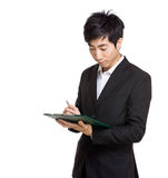 Asia businessman writing on file pad. Isolated on white Stock Photography