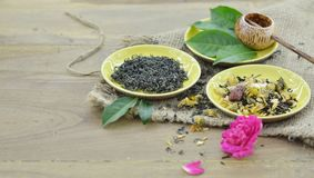 Asia of cultural- Dry tea. Assortment of dry tea and fresh tea leaves in plate on wooden background Royalty Free Stock Photo