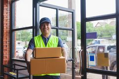 Asia delivery man are holding a cardboard box delivery to his cu Royalty Free Stock Photos