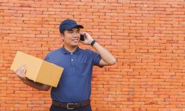Asia delivery man are holding a cardboard box delivery to his cu Stock Photography
