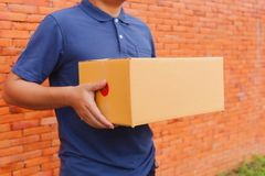 Asia delivery man are holding a cardboard box delivery to his cu Stock Photos