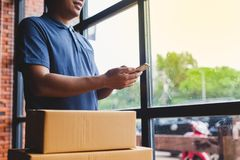 Asia delivery man are holding a cardboard box delivery to his cu Royalty Free Stock Image