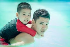 Asia. father and son swimmimng in the pool, happy. royalty free stock photos