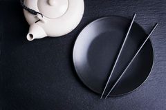 Asia food composition with chinese chopsticks, teapot and empty plate on a dark stone background Royalty Free Stock Photo
