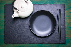 Asia food composition with chinese chopsticks, teapot and empty plate on a dark stone background Royalty Free Stock Images