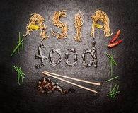 Asia food Inscription of noodles and sauce with chopstick and red chili on dark slate background Royalty Free Stock Image