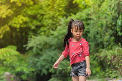 Asia Girl child in Red T-shirt looks down. In the forest Stock Photography