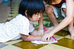 Asia girl  drawing paper on the floor Royalty Free Stock Photos